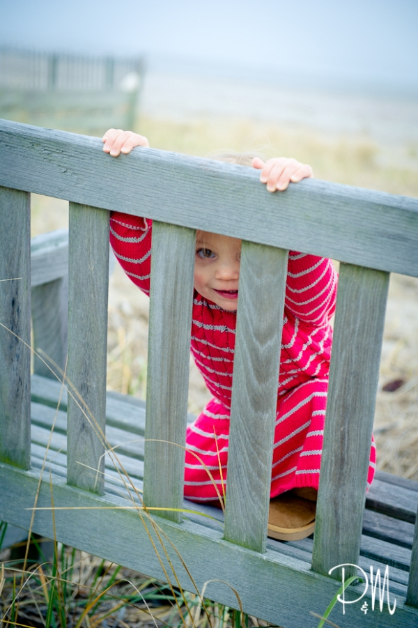 Girl peeking thru bench | Connecticut Children Photographer